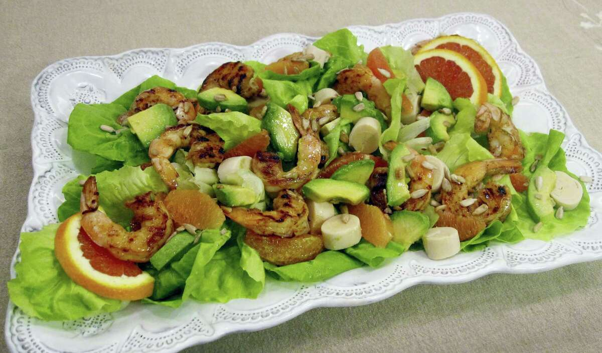 A salad of spicy grilled shrimp with hearts of palm, avocado and orange.
