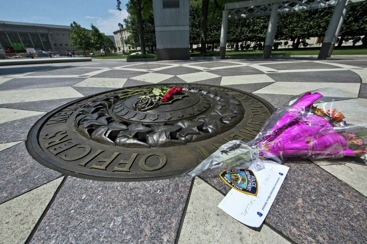 FILE - In this July 8, 2016 file photo, five red roses on the bronze medallion with another bouquet of flowers and a note in support of the Dallas Police Department are seen at The National Law Enforcement Officers Memorial in Washington. The number of police killed in the line of duty rose sharply in 2016, driven by shootings of police around the country, most notably ambushes in Dallas and Baton Rouge, Louisiana. From Jan. 1 through Wednesday, 135 officers lost their lives. Some died in traffic accidents, but nearly half were shot to death.