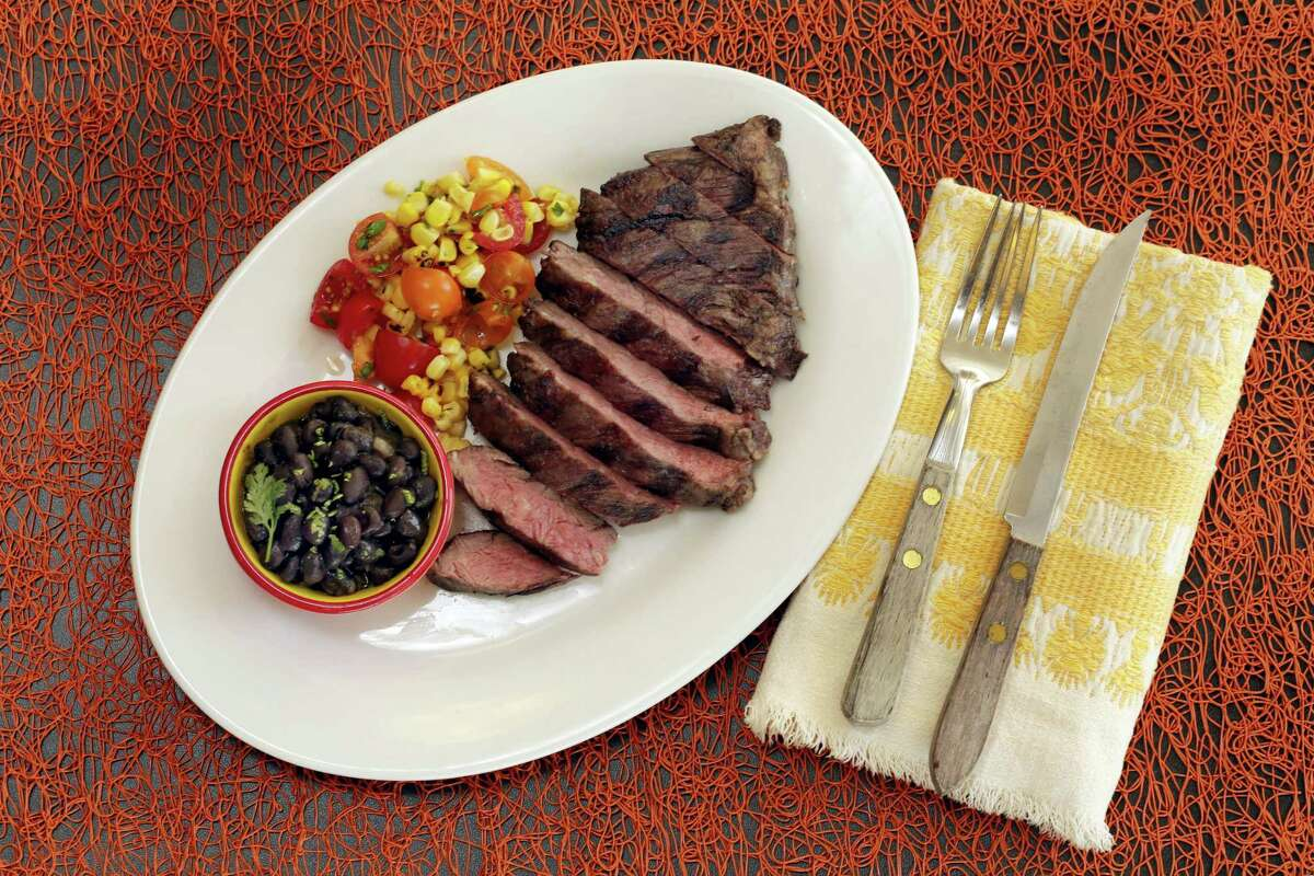 Skirt steak with beer-braised black beans and corn salsa.