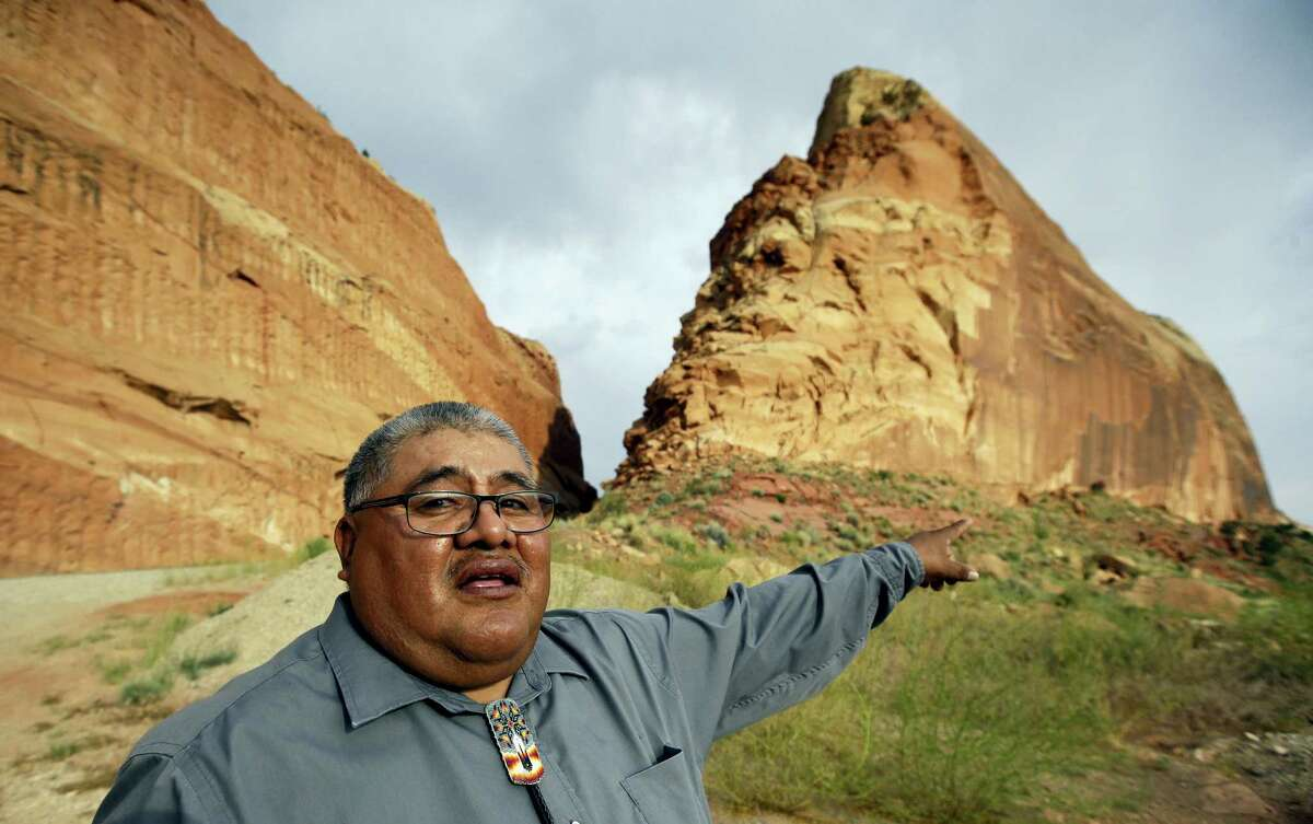 """FILE - This June 21, 2016, file photo, Malcolm Lehi, a Ute Mountain Tribal Commissioner points to a rock formation near Blanding, Utah. """"We don't want to forget about our ancestors,"""" said Lehi. """"Through them we speak. That's the whole concept of protecting and healing this land. They are still here among us as the wind blows."""" President Barack Obama designated two national monuments Wednesday, Dec. 28, at sites in Utah and Nevada that have become key flashpoints over use of public land in the U.S. West."""
