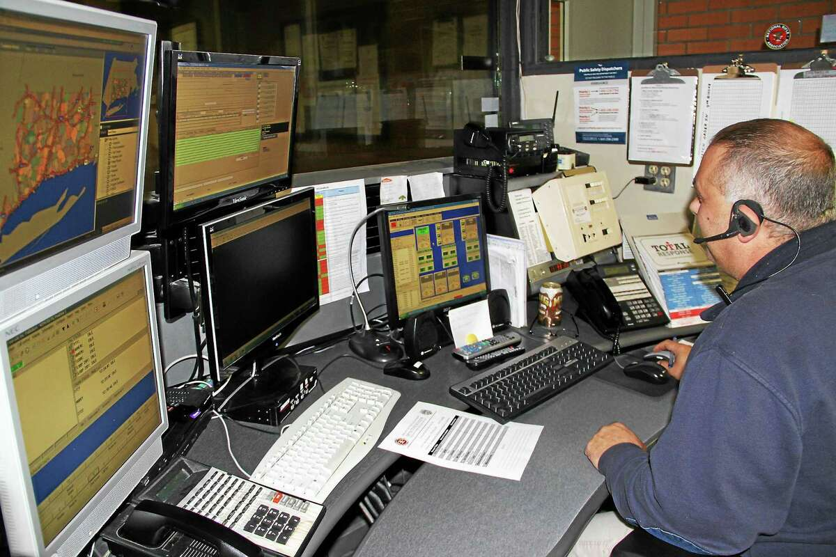 File photo - The Register Citizen Winsted Police Department dispatcher Philip Bascetta works the controls of the town's emergency communication system. The system broke down Monday; officials say they are now using a backup system.