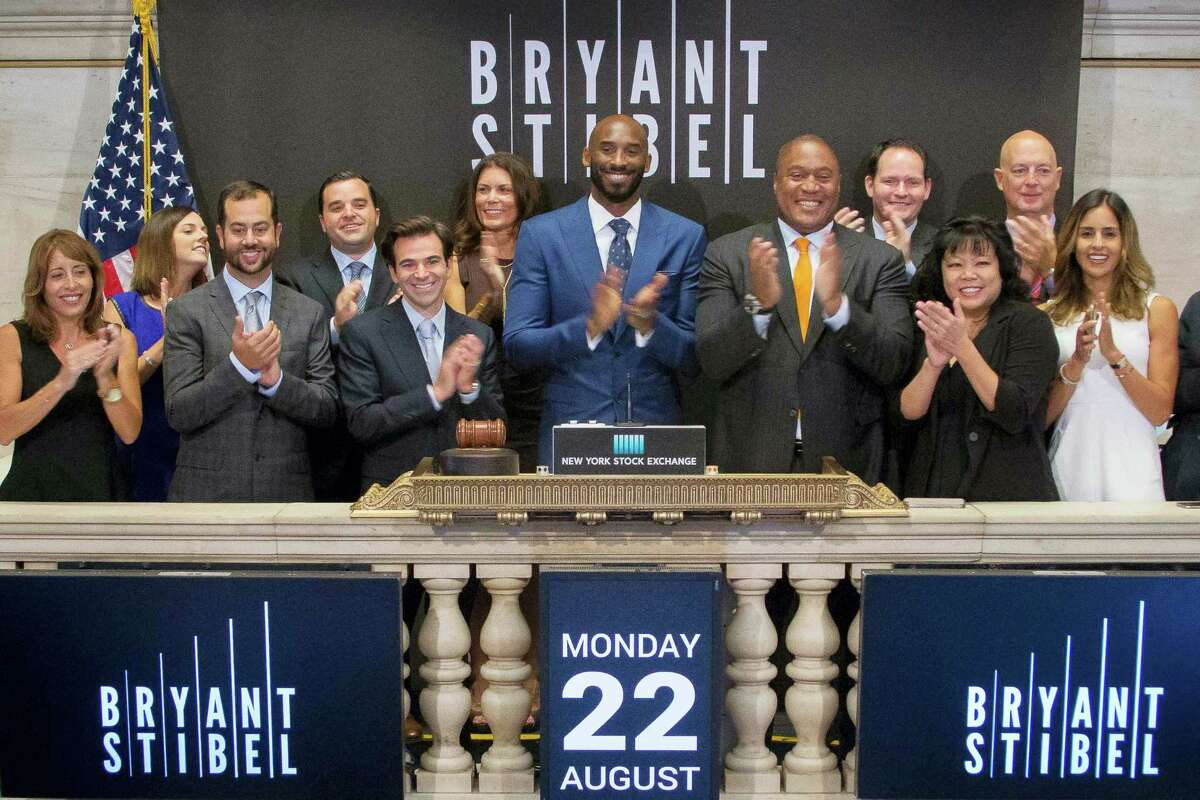 In this Monday photo provided by the New York Stock Exchange, retired NBA star Kobe Bryant, center, rings the opening bell with executives and guests of Bryant Stibel, at the NYSE in New York.