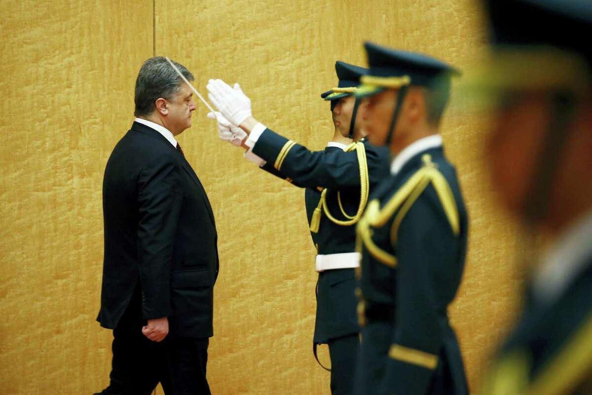 Ukrainian President Petro Poroshenko, left, inspects an honor guard before talks with Japan's Prime Minister Shinzo Abe at Abe's official residence in Tokyo on April 6, 2016. Poroshenko, who was in Japan to meet Abe and business leaders, defended himself earlier in the day in the massive leak of records on offshore accounts that has named political officials, business and celebrities from around the world.