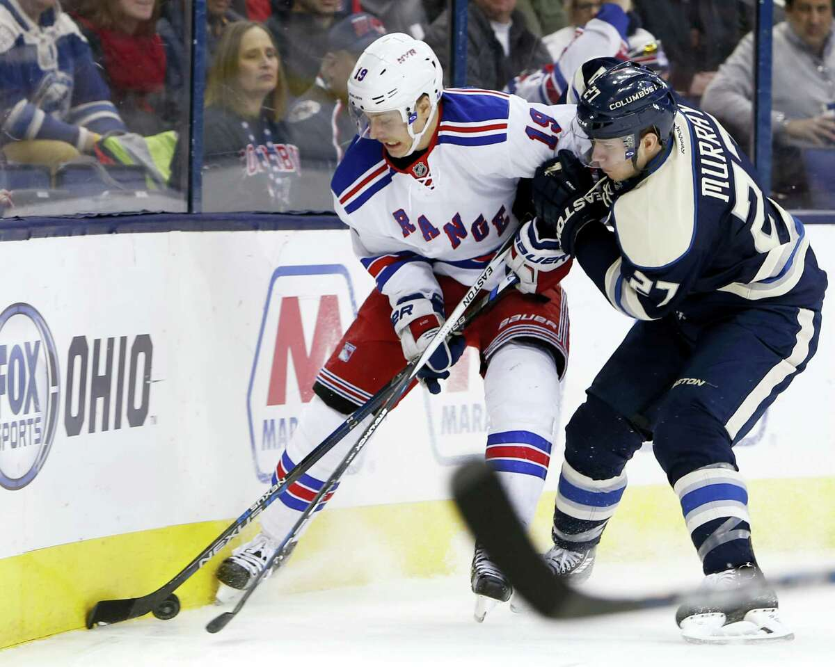 New York Rangers' Jesper Fast, left, of Sweden, and Columbus Blue Jackets' Ryan Murray fight for a loose puck during the first period of an NHL hockey game Monday, April 4, 2016, in Columbus, Ohio. (AP Photo/Jay LaPrete)