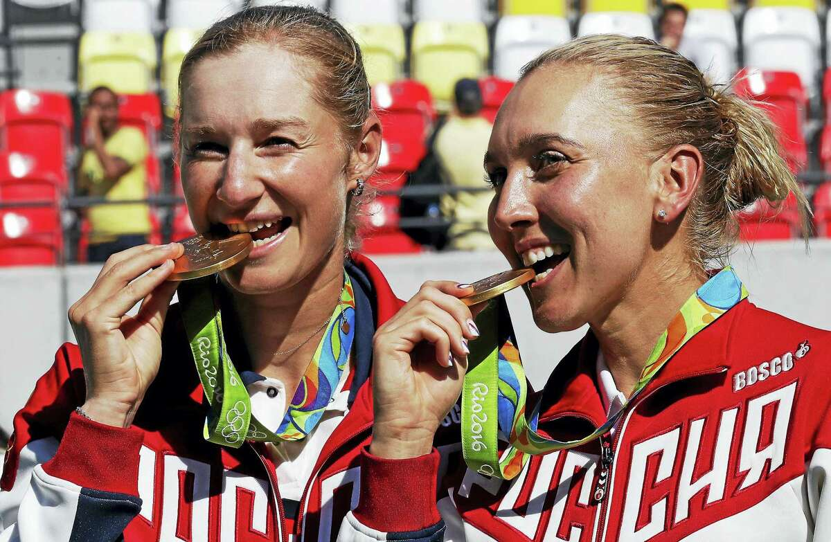 Russia's Elena Vesnina, right, and Ekaterina Makarova nibble on their gold medals in Rio.