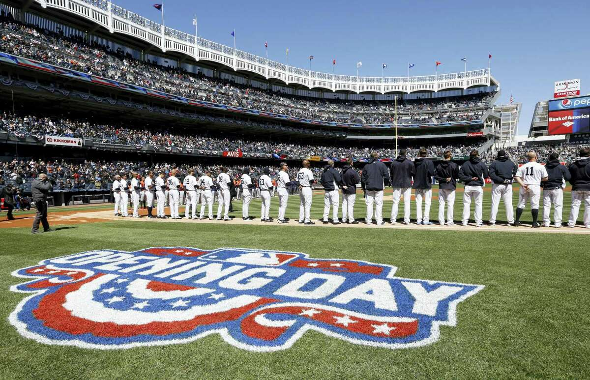 Yankees players stand on the baseline during the National Anthem on Tuesday at Yankees Stadium.