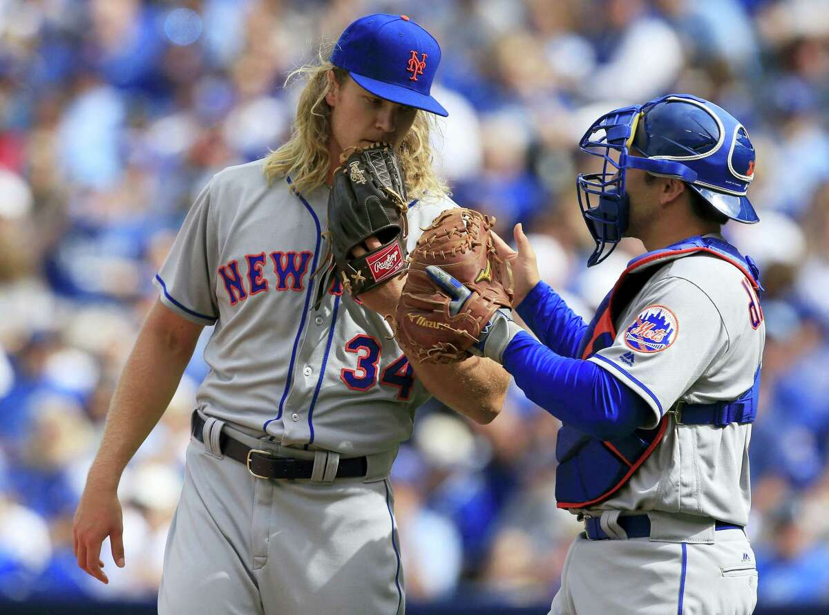 Noah Syndergaard talks with catcher Travis d'Arnaud, right, during the first inning on Tuesday.