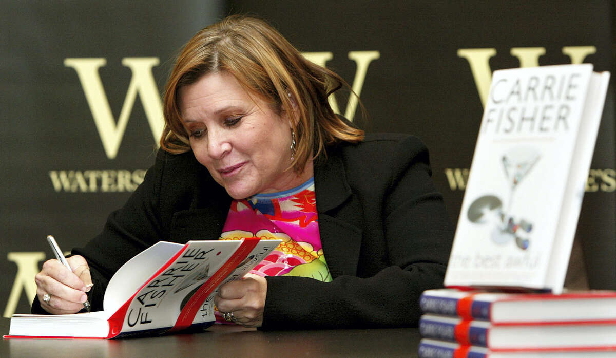 """FILE - In this Friday, Feb. 20, 2004 file photo, author Carrie Fisher autographs her new book """"The Best Awful"""" at a promotional event in London. On Tuesday, a publicist said Fisher has died at the age of 60."""