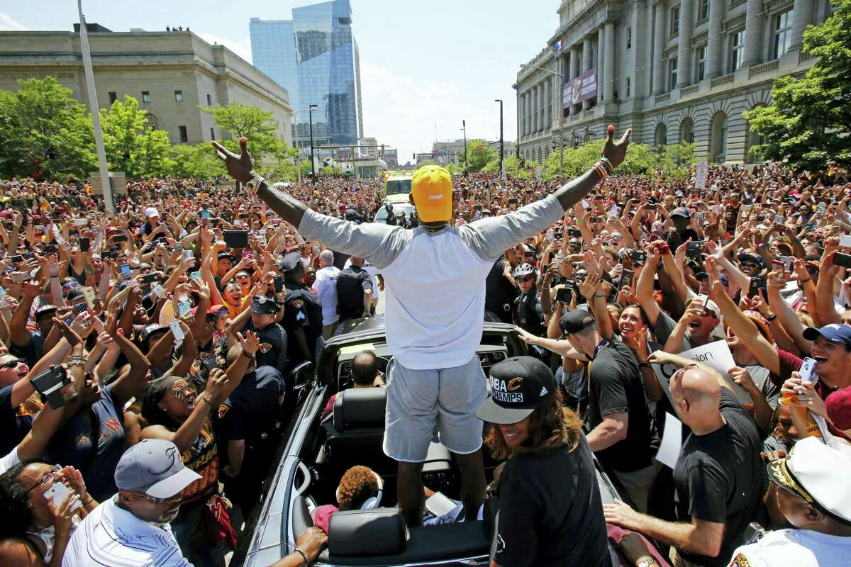 In this photo, Cleveland Cavaliers' LeBron James, center, stands in the back of a Rolls Royce as it makes its way through the crowd lining the parade route in downtown Cleveland, celebrating the basketball team's NBA championship. On Tuesday, Dec. 27, James, who ended 52 years of sports heartache by bringing Cleveland a championship and used his superstar platform to address social causes, was chosen as The Associated Press 2016 Male Athlete of the Year.
