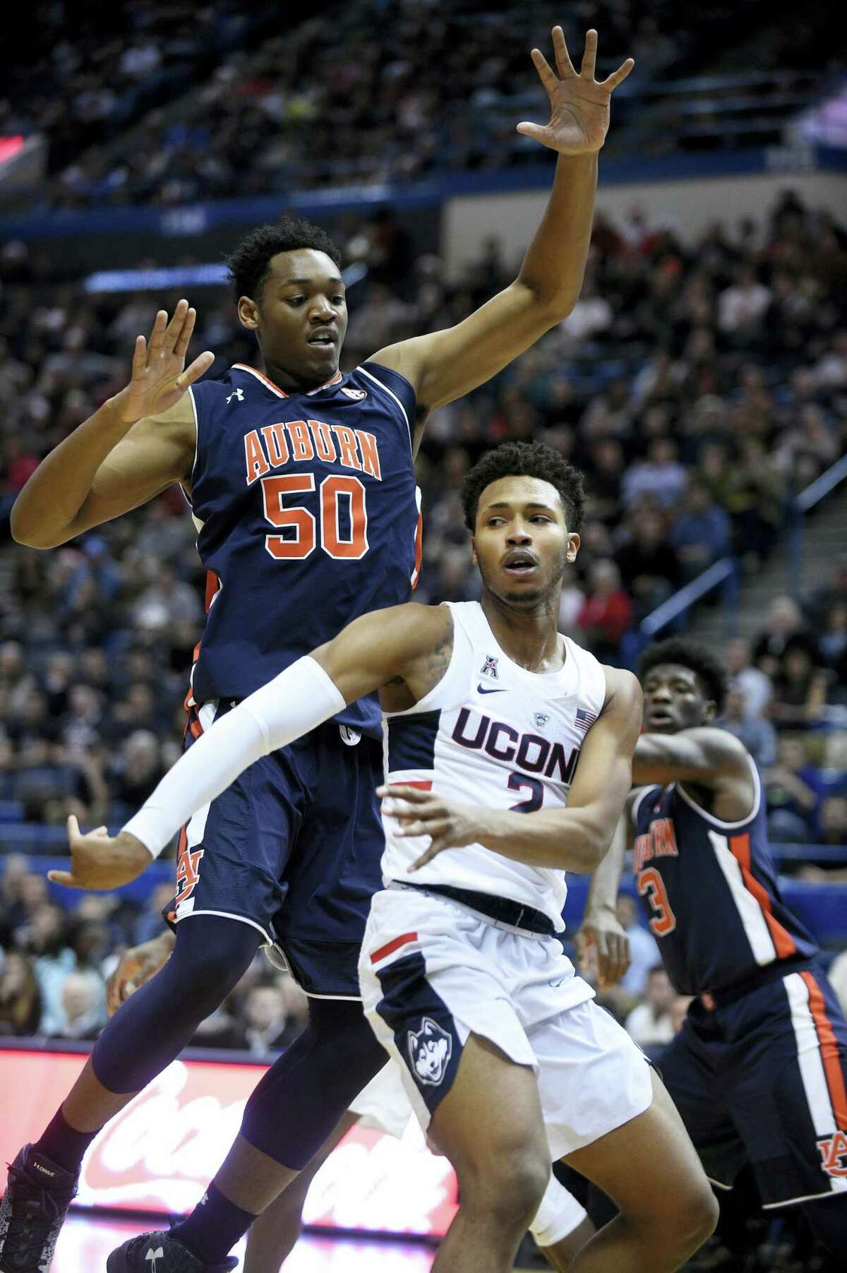 Connecticut's Jalen Adams (2) is guarded by Auburn's Austin Wiley (50). Adams suffered a concussion during Friday's overtime loss to Auburn.