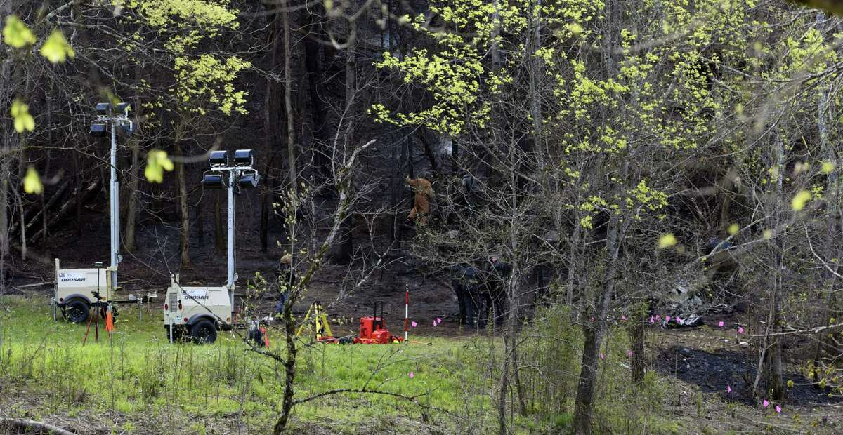 Officials investigate where a sightseeing helicopter crashed, Tuesday, April 5, 2016, near Sevierville, Tenn. Officials said five died when the aircraft operated by Smoky Mountain Helicopters crashed Monday near the Great Smoky Mountains National Park.