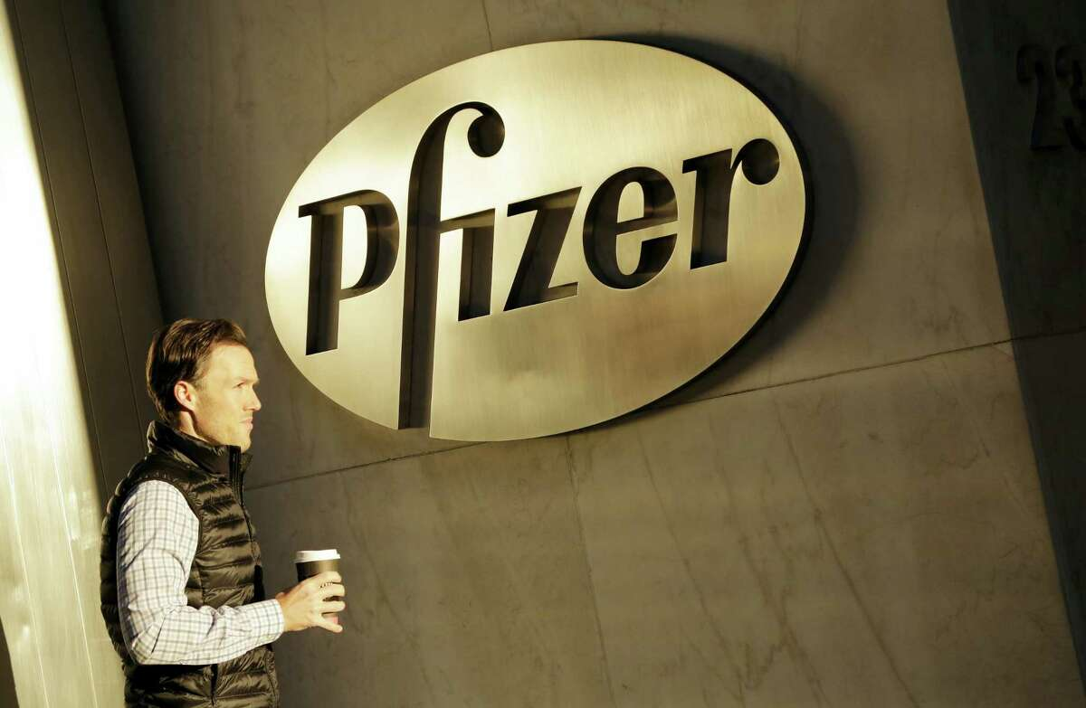 In this Monday, Nov. 23, 2015 photo, a man enters Pfizer's world headquarters, in New York. Pfizer is buying biopharmaceutical company Medivation in a deal valued at about $14 billion.