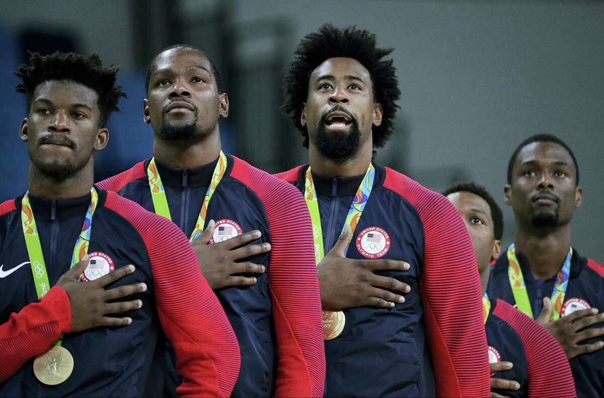 Members of the United States' basketball team stand for the national anthem after accepting their gold medals on Sunday.