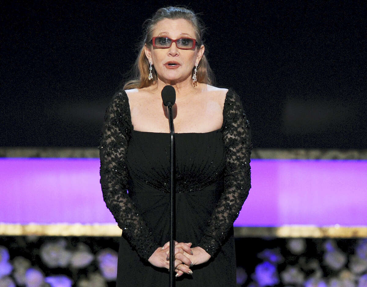 In this Sunday file photo, Carrie Fisher presents the life achievement award on stage at the 21st annual Screen Actors Guild Awards at the Shrine Auditorium in Los Angeles. Fisher has reportedly been transported to a hospital after suffering a severe medical emergency on a flight Friday.