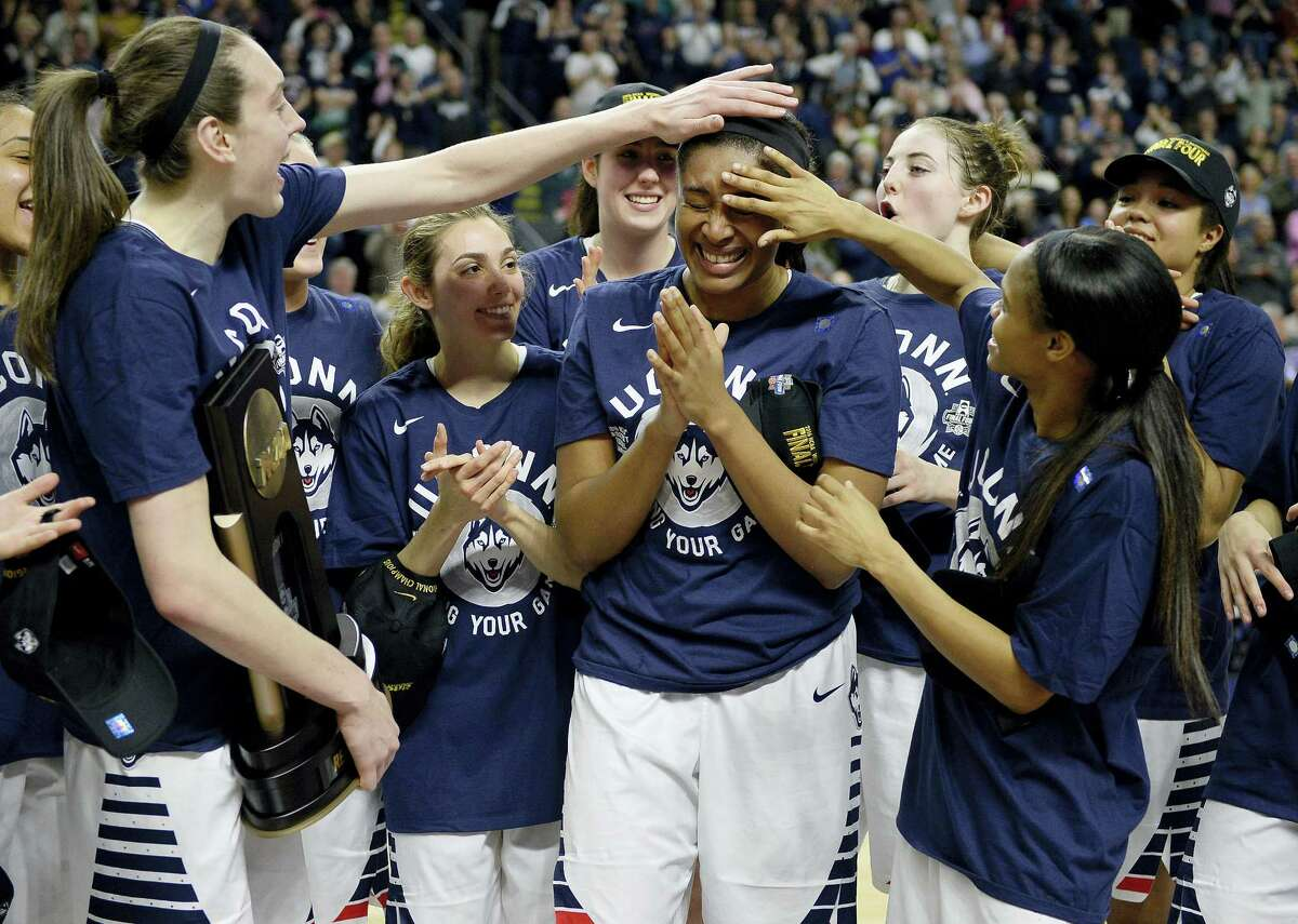 Connecticut's Breanna Stewart, left, and Moriah Jefferson, right, celebrate with Morgan Tuck, center, after winning 86-65 over Texas in a college basketball game in the regional final of the women's NCAA Tournament, Monday, March 28, 2016, in Bridgeport, Conn. (AP Photo/Jessica Hill)