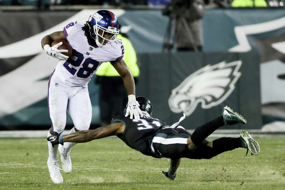 New York Giants' Paul Perkins, left, tries to dodge Philadelphia Eagles' Jalen Mills during the second half of an NFL football game, Thursday, Dec. 22, 2016, in Philadelphia. (AP Photo/Michael Perez)