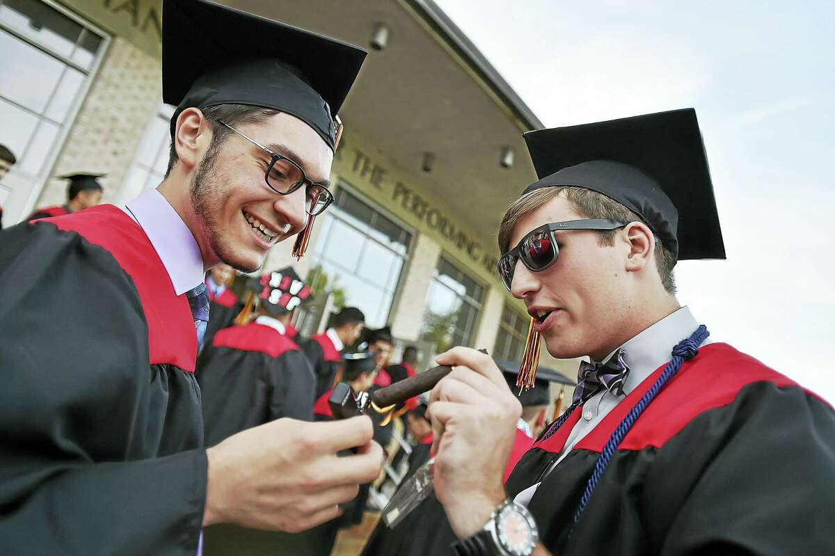 Members of Platt Technical High School class of 2016, Joseph Fraulo and Mike Iozzo light up cigars following ommencement exercises on Wednesday, June 15, 2016 at the John Lyman Center for the Performing Arts at Southern Connecticut State University.