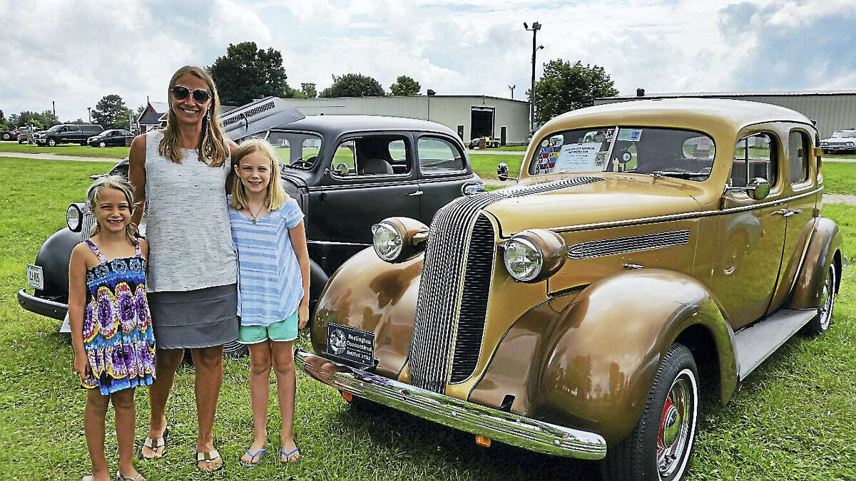 N.F. Ambery Jessica Bannerman of Norfolk and her daughters McKenzie, 7, and Carley, 9, pause near a gold 1936 Pontiac Master Six Cabriolet owned by Arthur and Marcia Scheidel of Burlington.
