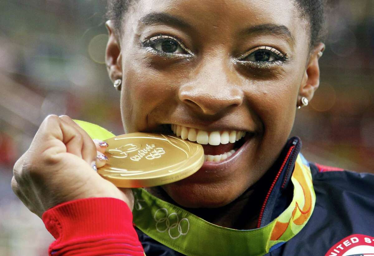 Simone Biles bites her gold medal for the artistic gymnastics women's individual all-around final at the 2016 Summer Olympics.