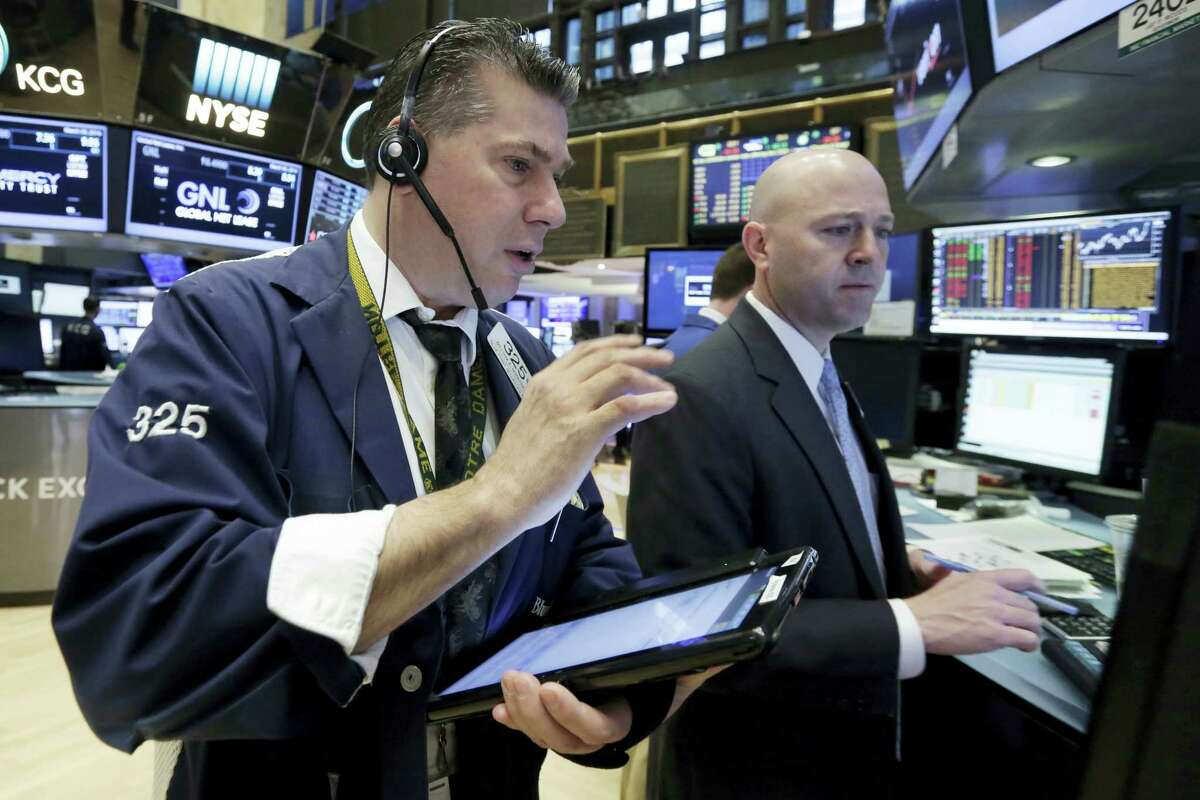 Trader William McInerney, left, and specialist Jay Woods work on the floor of the New York Stock Exchange recently.