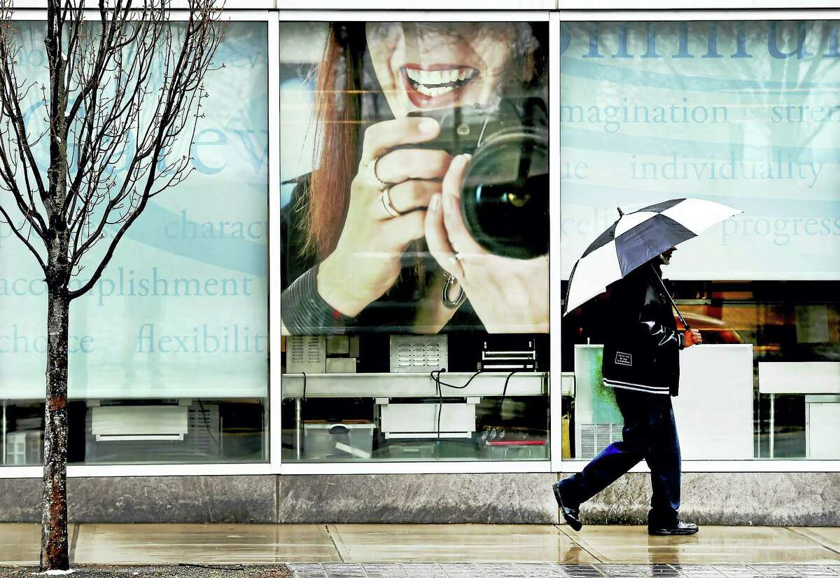 A passer-by braves the chilly rain Monday morning as he walks near Gateway Community College on Church Street near George Street in New Haven.
