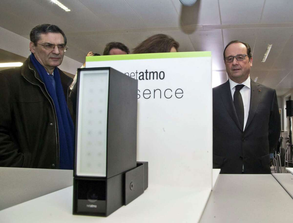 "French President Franocis Hollande, right, and French politician Patrick Devedjian, left, listening speaks as he visits a tech company in Boulogne-Billancourt, outside Paris on April 4, 2016. French president says the Panama revelations are ""good news"" because it will help the state to recover money from people who have committed tax evasion."