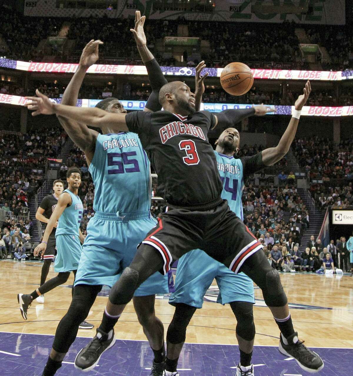 Chicago Bulls' Dwyane Wade (3) loses the ball as he drives between Charlotte Hornets' Roy Hibbert (55) and Michael Kidd-Gilchrist (14) in the second half of an NBA basketball game in Charlotte, N.C., on Dec. 23, 2016. The Hornets won 103-91.