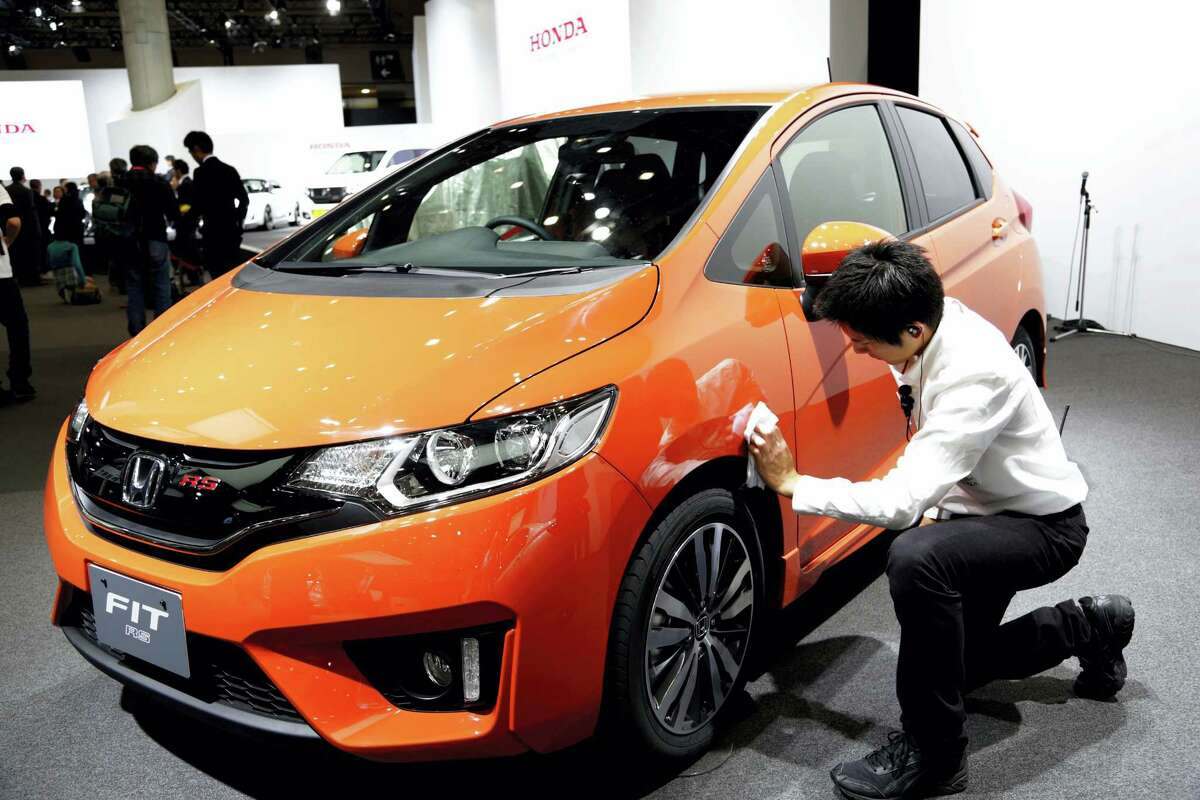 In this Nov. 20, 2013 photo, a worker wipes a Honda Fit during the media preview for the Tokyo Motor Show at Tokyo Big Sight convention hall in Tokyo. Honda recalled 160,000 Fit subcompact and Vezel sport-utility vehicles, manufactured from August 2013 through February 2016, in Japan on April 3, 2016 because of defective power steering and a part that controls the electric current in the vehicles.
