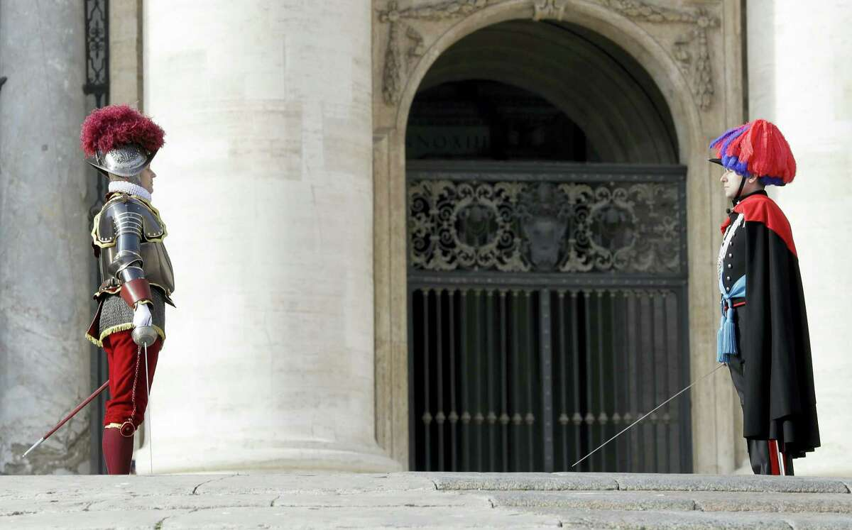 A Swiss Guard left, and a Carabinieri officer stand guard in front of Peter's Basilica at the Vatican on Sunday, Dec. 25, 2016. Saturday's late night Mass was the first major event of the Christmas season, followed by Francis' noon Urbi et Orbi (To the city and the world) blessing on Christmas day.
