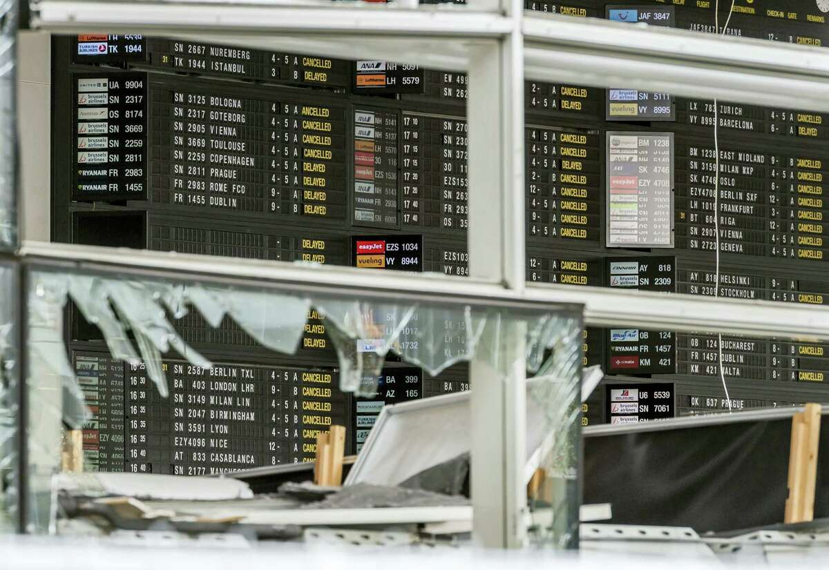 This March 23, 2016 photo shows an arrivals and departure board behind blown out windows at Zaventem Airport in Brussels. The airport plans to be back up to 20 percent of capacity by Monday, April 4, 2016.
