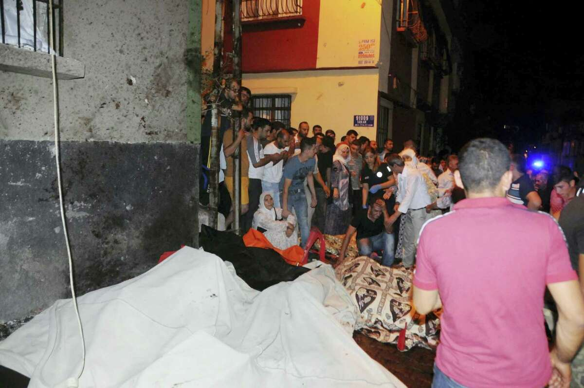 People react after an explosion in Gaziantep, southeastern Turkey, early Sunday, Aug. 21, 2016. Gaziantep Province Gov. Ali Yerlikaya said the deadly blast, during a wedding near the border with Syria, was a terror attack.