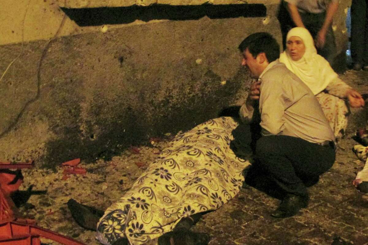 A man cries over a covered body after an explosion in Gaziantep, southeastern Turkey, late Saturday, Aug. 20, 2016. Gaziantep Province Gov. Ali Yerlikaya said the deadly blast, during a wedding near the border with Syria, was a terror attack.