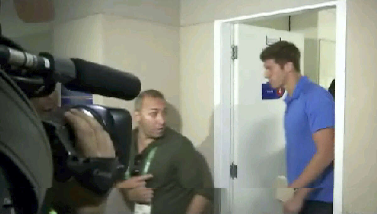 This still image taken from video shows U.S. swimmer James Feigen leaves a court meeting, early Friday, Aug. 19, 2016, in Rio de Janeiro, Brazil. Two American Olympic swimmers, Gunnar Bentz and Jack Conger, were on their way home Friday after being pulled off a plane a day earlier to testify about an alleged robbery at the Rio Olympics that Brazilian police said was made up. The lawyer for Feigen said he would make a $10,800 payment and leave Brazil later in the day.