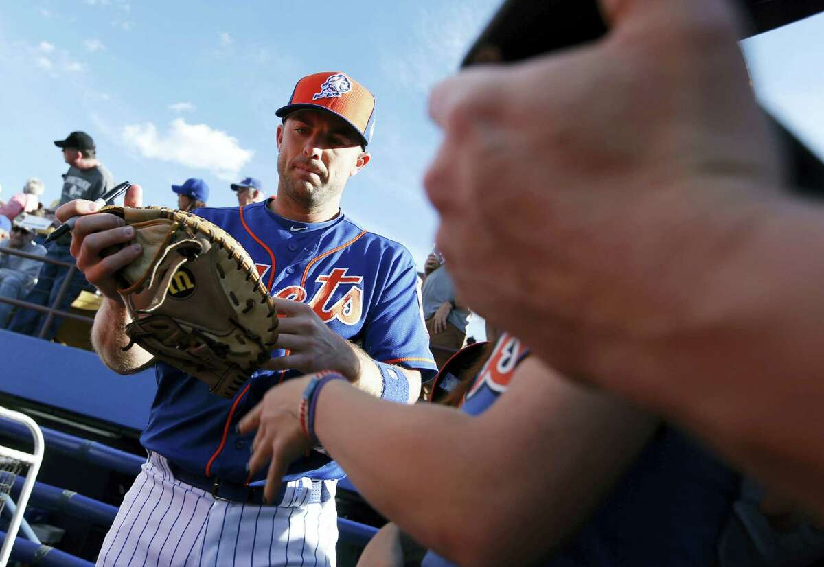 The Mets' David Wright signs autographs for fans before an exhibition game against the Cubs on Thursday.