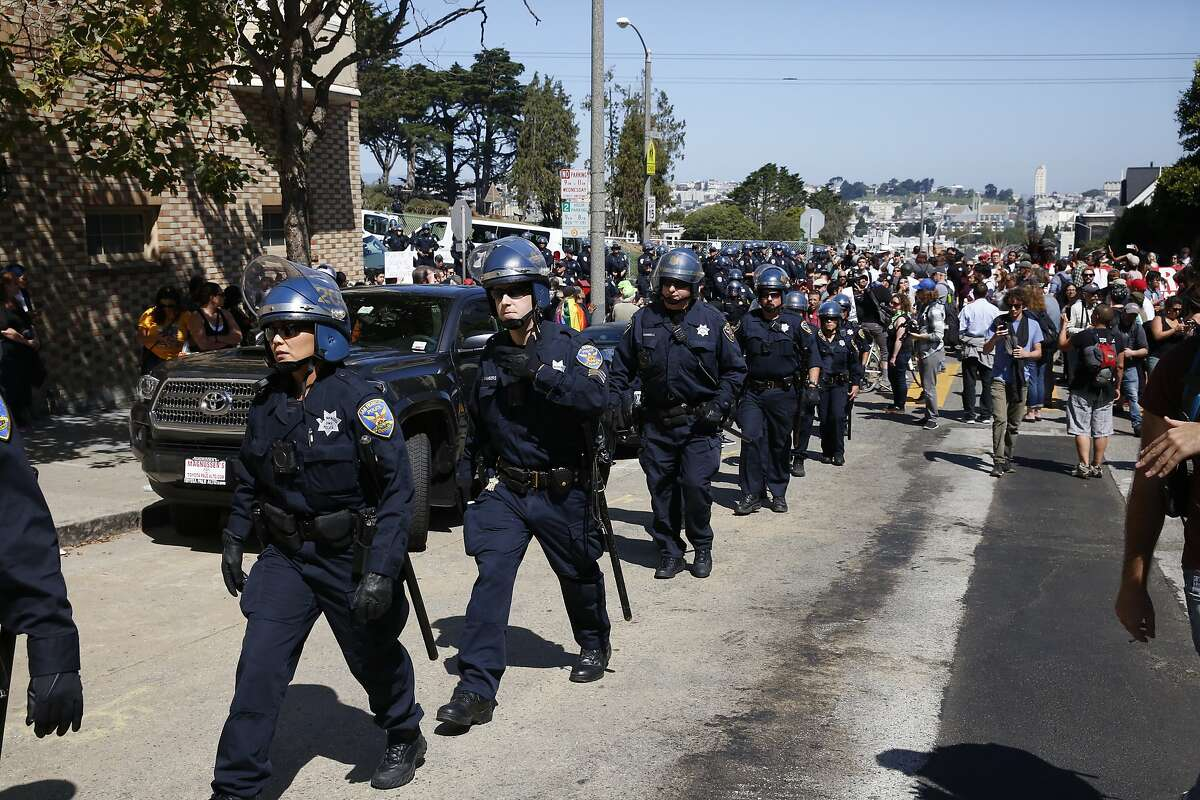 SFPD officers move toward a barricade from Alamo Square to reinforce it against more protesters on Saturday, Aug. 26, 2017 in San Francisco, Calif.