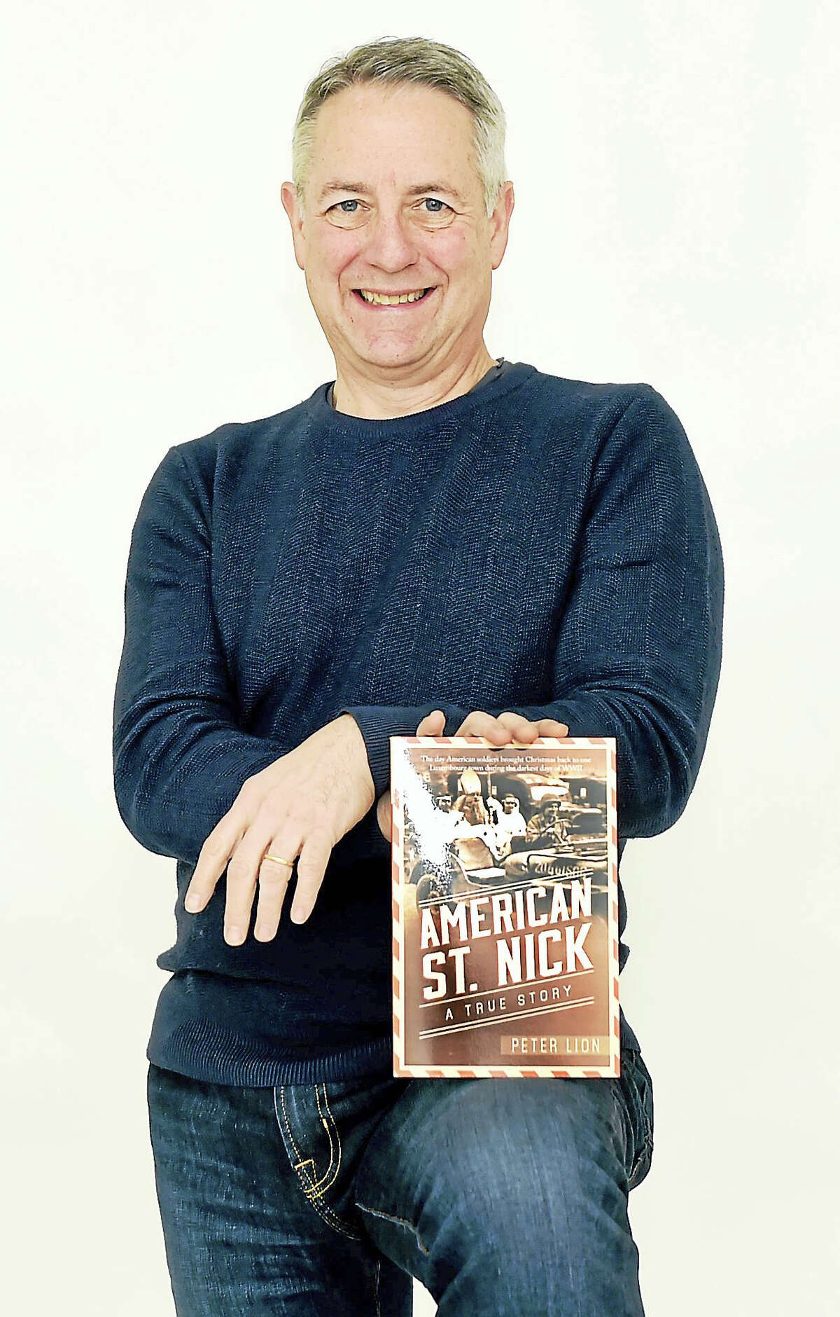 Author Peter Lion shows off his non-fiction book that tells the story of American soldiers bringing Christmas gifts to children in Luxembourg during World II.