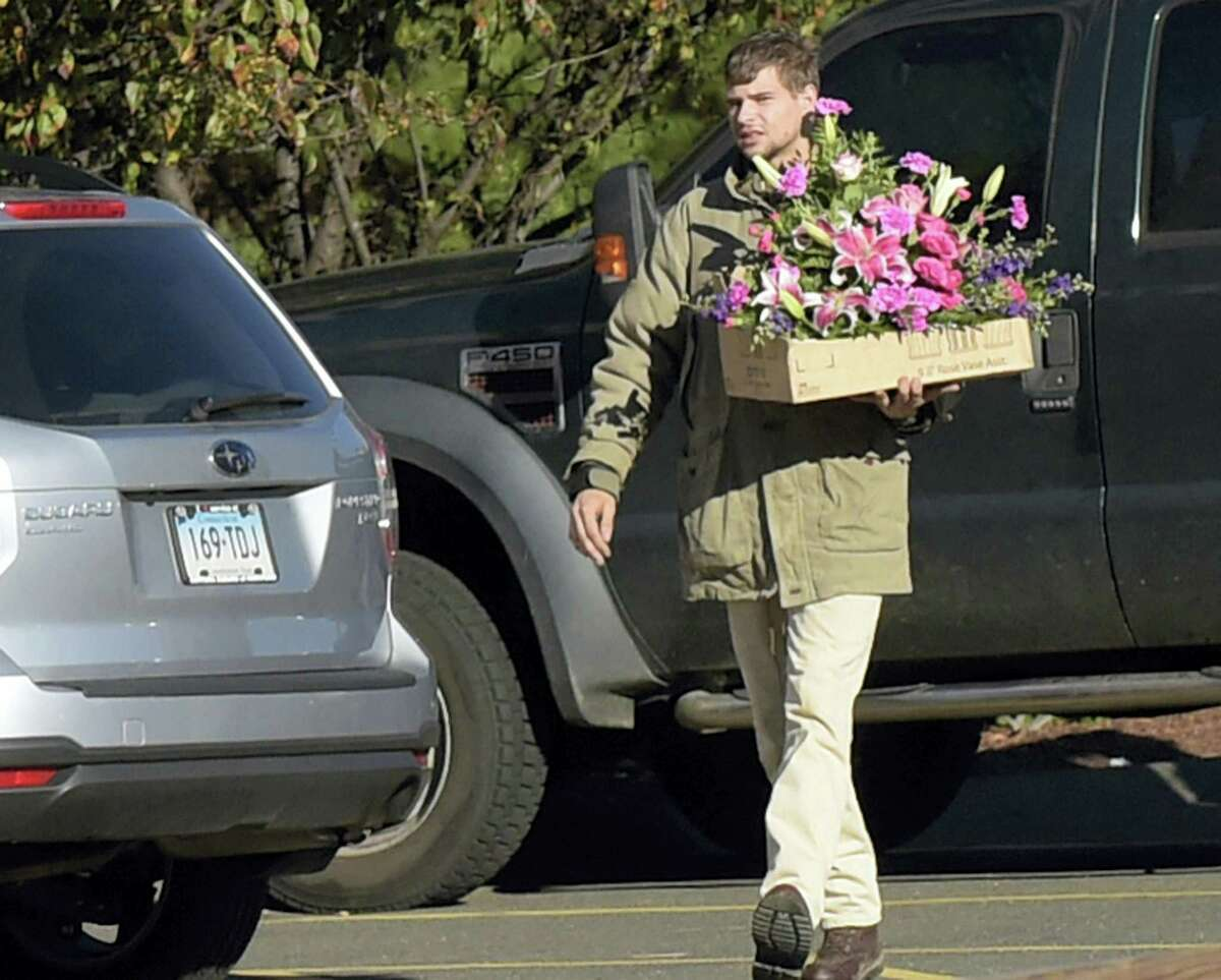 In this file photo, Nathan Carman carries flowers to a memorial service for his mother Linda Carman, at Saint Patrick - Saint Anthony Church in Hartford. Nathan Carman spent a week at sea in a life raft before being rescued by a passing freighter. His mother who accompanied him on their ill-fated September fishing trip was missing and presumed dead.