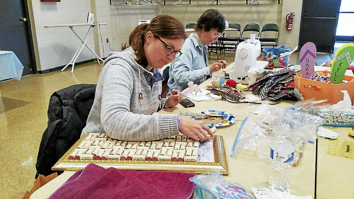 Perry Diciccio of Middletown created a corkboard made of wine corks while her mother Kyle Diciccio of Wethersfield sews homemade coin purses during the semi-annual Flip Flop Crop crafting event at Coe Memorial Park Civic Center in Torrington on Saturday.