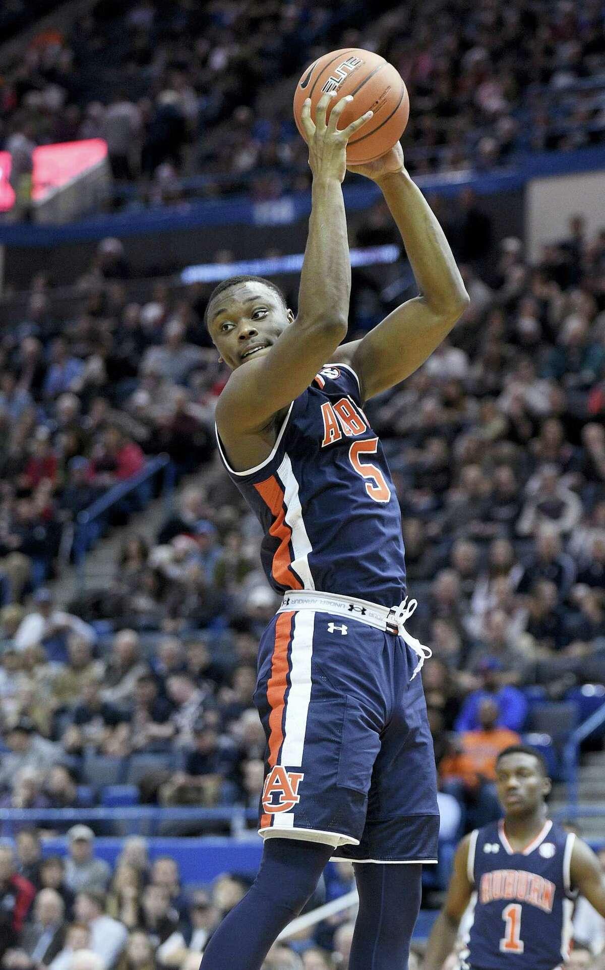 Auburn's Mustapha Heron grabs a rebound during Friday's game against UConn in Hartford.