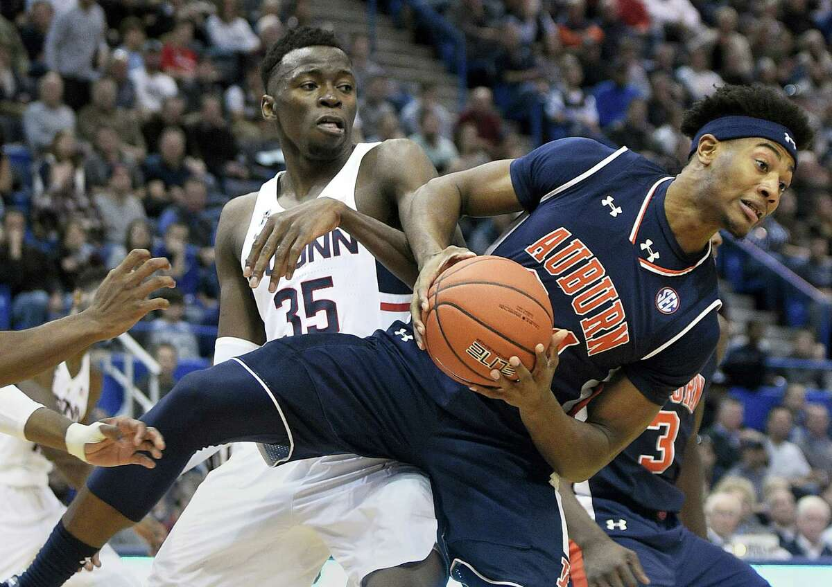 Auburn's Anfernee McLemore, right, fights for a rebound with UConn's Amida Brimah.