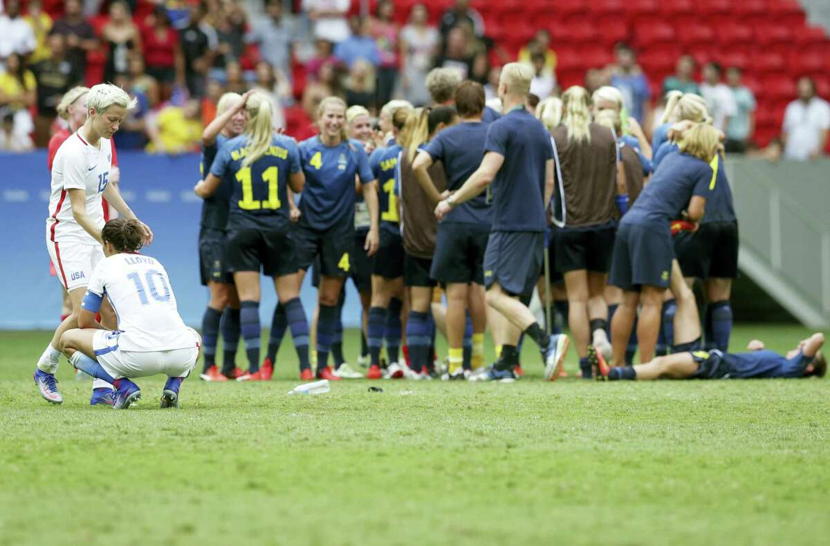Megan Rapinoe and Carli Lloyd react as Sweden's players celebrate after winning a quarterfinal match at the Olympics in Rio.