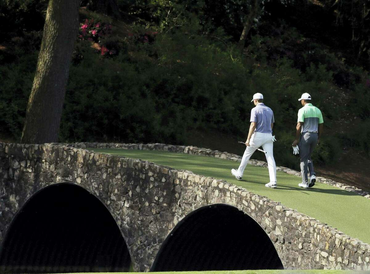Tiger Woods, right, walks across the Ben Hogan Bridge with Jordan Spieth during a practice round for last year's Masters. Woods will not play in this year's Masters because of a back injury.