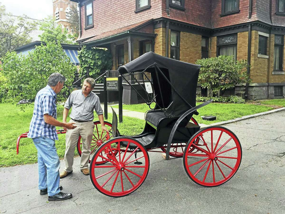 Ben Lambert - The Register Citizen Mark McEachern, right, executive director of the Torrington Historical Society, talks with Stan Machuszek of Saddlebrook, New Jersey, who brought a carriage made by H. Pulver & Son in Torrington in the late 1890s that he restored and donated on Wednesday.