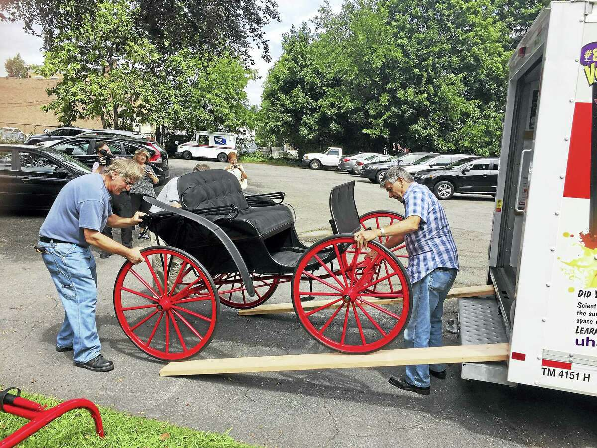 Ben Lambert - The Register Citizen A Torrington-crafted horse-drawn carriage, recently restored by Stan Machuszek of Saddlebrook, New Jersey, was donated to the city Historical Society Wednesday. Above, Machuszek and a friend unload the carriage at the historical society Wedneday.