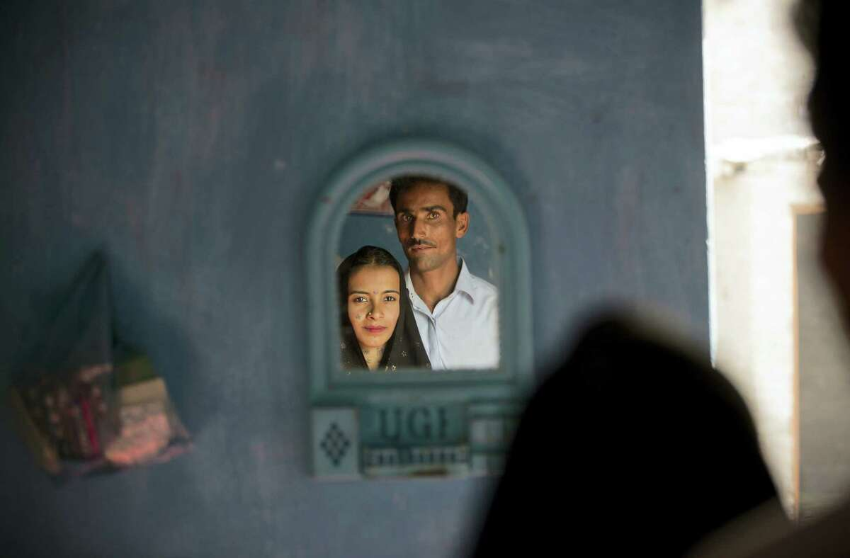 Hamid Brohi poses for a picture with his wife Jeevti at their home in Pyaro Lundh, Pakistan. The night Jeevti disappeared, her family slept outside to escape Pakistan's brutal summer heat; in the morning she was gone, snatched by a wealthy landlord to whom her parents owed $1,000 dollars. She is one of the estimated 1,000 Christian and Hindu girls taken from their homes every year in Pakistan for supposed repayments of debt, most of them ending up married off to older men and forcibly converted to Islam.