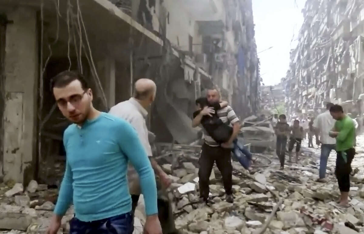 In this image made from video, a man carries a child after airstrikes hit Aleppo, Syria.