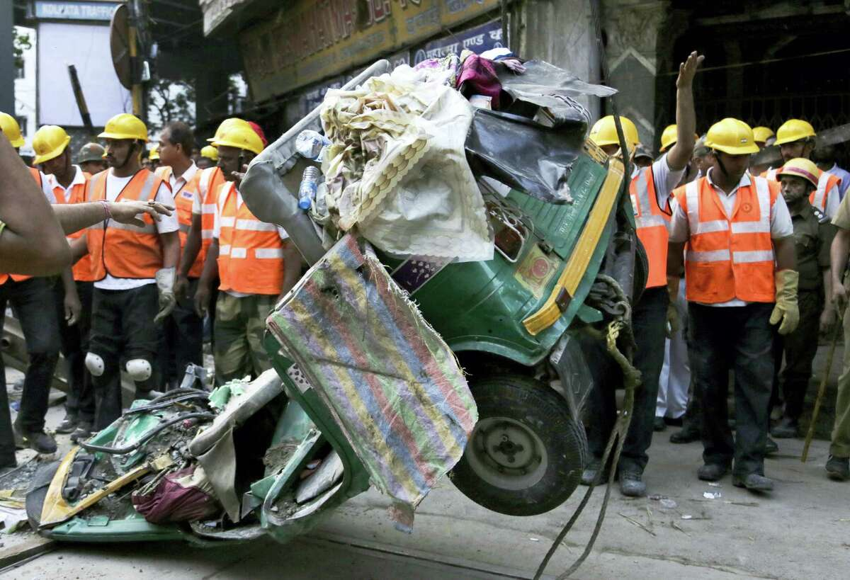 A damaged three-wheeled vehicle is taken out from the rubble of a collapsed overpass in Kolkata, India, Friday, April 1, 2016. The overpass spanned nearly the width of the street and was designed to ease traffic through the densely crowded Bara Bazaar neighborhood in the capital of the east Indian state of West Bengal. About 100 meters (300 feet) of the overpass fell, while other sections remained standing.