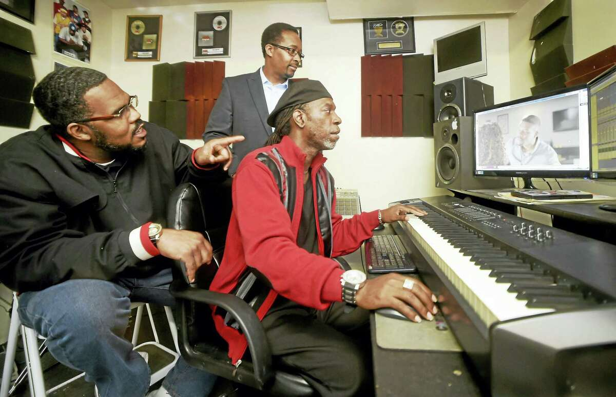 """Composer Kenneth Hampton of Branford, founder and co-CEO of Raise Em Up Records and the founder, CEO and composer at C.M.G. (Composers Media Group) LLC, right, looks at a feature film project with Raise Em Up Records vice presidents and childhood friends Clifton V. Powell of Meriden, left, and David """"Swing"""" Edwards of Hamden, right, at Hampton's Branford recording studio."""