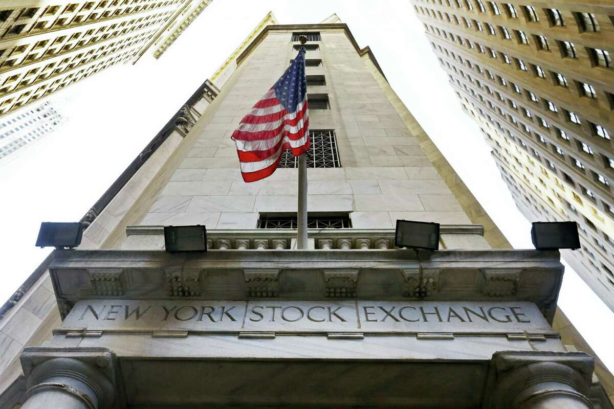 In this Friday file photo, the American flag flies above the Wall Street entrance to the New York Stock Exchange.