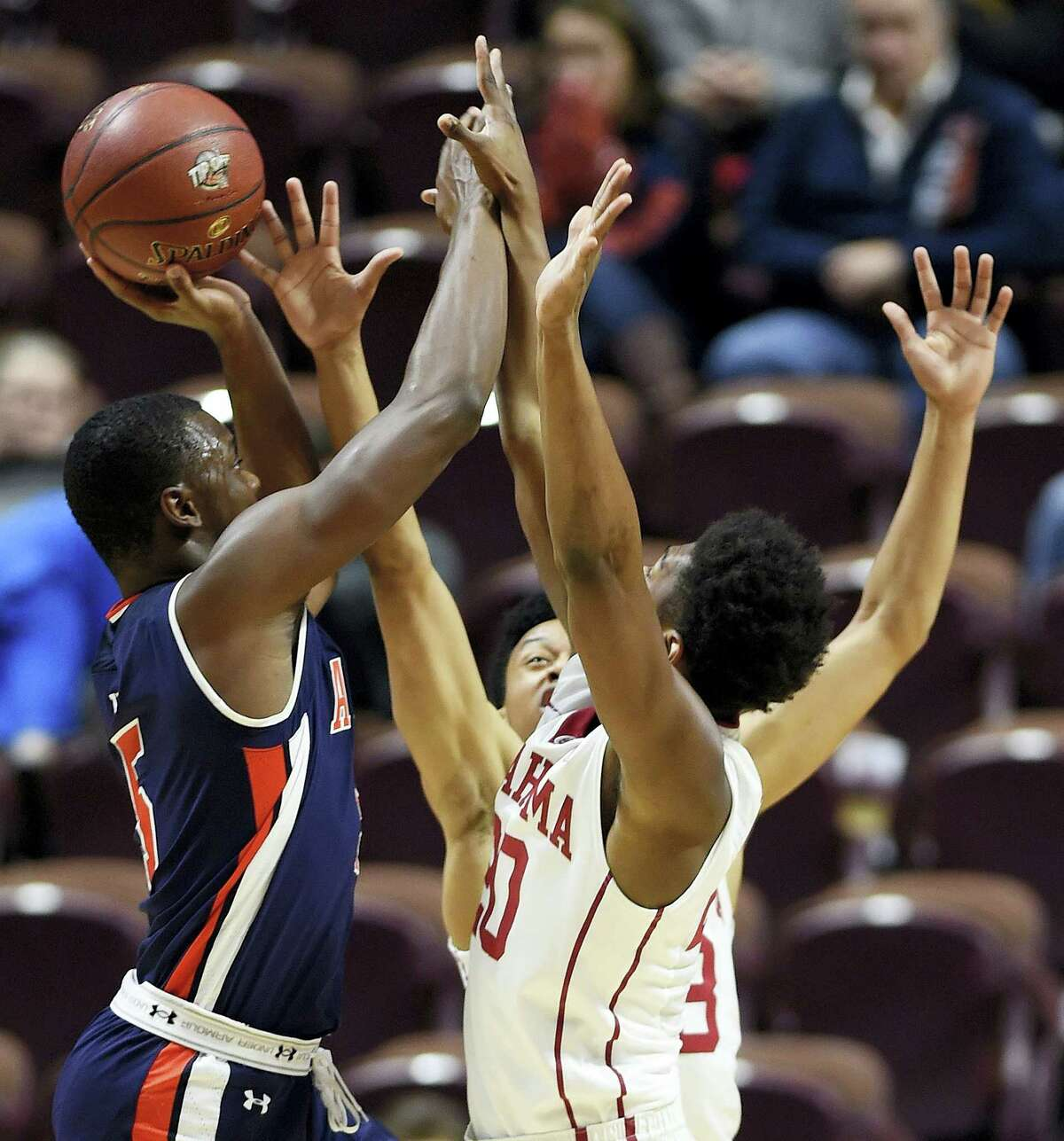 Auburn's Mutapha Heron (5) shoots over Oklahoma defenders Marshall Thorpe, front, and Jordan Shepard, back, during Wednesday's game at the Mohegan Sun Arena in Uncasville.